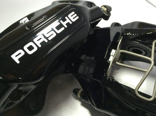 Black Porsche brake caliper with old Porsche decals in white