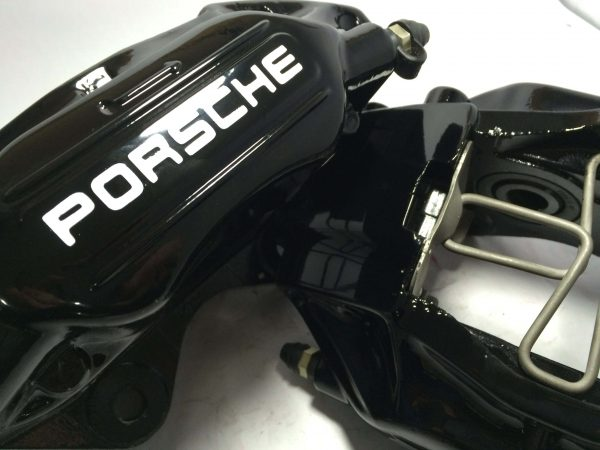Black Porsche brake caliper with old Porsche decals in white